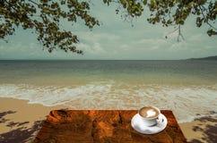 Кофе питья горячий около моря Стоковые Изображения