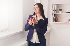 Кофе питья женщины около окна на рабочем месте Стоковые Фото