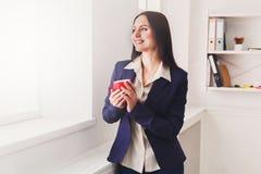 Кофе питья женщины около окна на рабочем месте Стоковое Фото