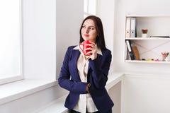 Кофе питья женщины около окна на рабочем месте Стоковые Изображения RF