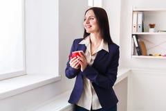 Кофе питья женщины около окна на рабочем месте Стоковое фото RF