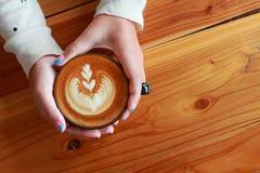 Кофе питья женщины руки красоты горячий на коричневом цвете деревянном Стоковое фото RF