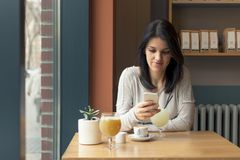 Кофе питья молодой женщины и smartphone пользы на кафе стоковая фотография rf