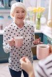 Кофе пожилой женщины выпивая в кухне и говорить Стоковое Фото