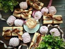 Кофе положен вне на таблицу с розовыми зефирами и подарками с коричневым смычком стоковое изображение rf