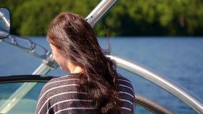 Кофе привлекательной молодой женщины брюнет выпивая пока курсирующ на шлюпке на озере акции видеоматериалы