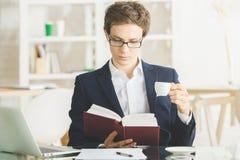 Кофе привлекательного бизнесмена выпивая и книга чтения Стоковые Изображения