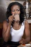 Кофе привлекательной Афро-американской женщины выпивая Стоковые Изображения
