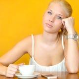 Кофе привлекательной белокурой девушки выпивая на кафе Стоковые Изображения