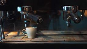 Кофе сделанный в профессиональной машине эспрессо лить в чашку стоковое фото rf