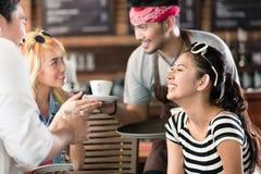 Кофе сервировки кельнера в азиатском кафе к женщинам и человеку Стоковое Изображение RF