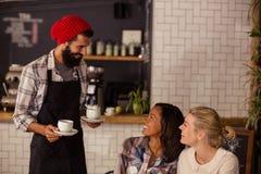 Кофе сервировки кельнера и взаимодействовать с клиентами Стоковое фото RF