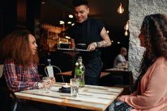 Кофе сервировки кельнера к клиентам на кафе Стоковое фото RF