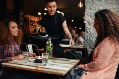Кофе сервировки кельнера к молодым женщинам на кафе Стоковые Фотографии RF