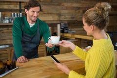 Кофе сервировки Barista к женскому клиенту в столовой Стоковое Фото