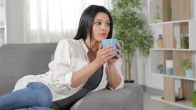 Кофе серьезной женщины выпивая дома видеоматериал