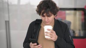 Кофе сети человека занимаясь серфингом и выпивая на железнодорожной платформе акции видеоматериалы