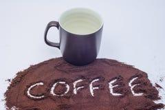Кофе сказал по буквам в землях кофе с коричневой кружкой стоковое изображение