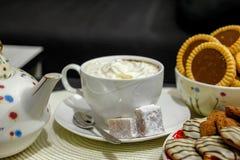 Кофе со сливками и торты на таблице стоковое фото