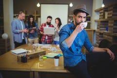 Кофе стильного бизнесмена выпивая пока сидящ на таблице Стоковые Изображения