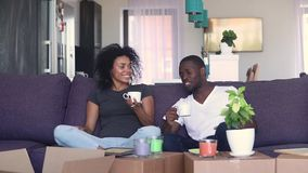 Кофе счастливых африканских пар выпивая распаковывая коробки в новом доме сток-видео