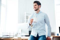 кофе счастливого бизнесмена выпивая в офисе Стоковая Фотография RF