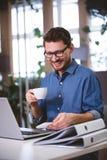 Кофе счастливого бизнесмена выпивая смотря мобильный телефон в творческом офисе Стоковые Изображения RF