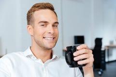 Кофе счастливого красивого молодого бизнесмена выпивая в офисе Стоковое Изображение RF