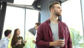 Кофе счастливого attracive молодого бизнесмена выпивая в офисе Стоковые Фотографии RF