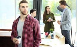 Кофе счастливого attracive молодого бизнесмена выпивая в офисе Стоковое фото RF