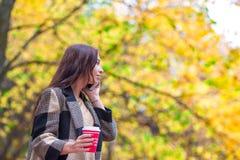 Кофе счастливой красивой женщины выпивая в парке осени под листопадом Стоковое Изображение