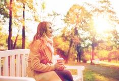 Кофе счастливой молодой женщины выпивая в парке осени Стоковая Фотография RF