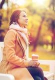 Кофе счастливой молодой женщины выпивая в парке осени Стоковые Изображения