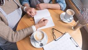 Кофе счастливых пар выпивая и работа таблицей Стоковое Изображение