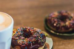 Кофе с вычерченными сердцем и молоком на деревянном столе в кофейне 2 donuts шоколада с разбрасывать на таблицу рядом с стоковое изображение rf