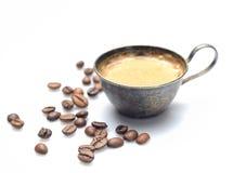 Кофе с молоком в винтажной чашке металла, зажаренных в духовке кофейных зернах на белой предпосылке стоковое фото