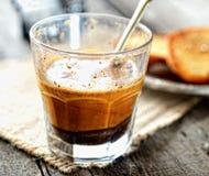 Кофе с молоком в стекле с ложкой на салфетке на серой деревянной предпосылке стоковая фотография rf