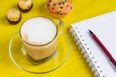 Кофе с тетрадью на желтой таблице Стоковое Изображение RF