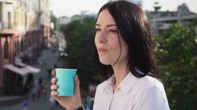 Кофе уверенно бизнес-леди выпивая отдыхая и усмехаясь на городской улице акции видеоматериалы