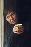 Кофе унылой одной женщины выпивая в темной комнате Стоковая Фотография RF