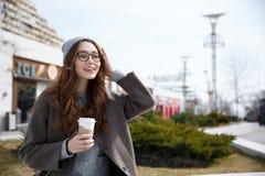 Кофе усмехаясь женщины идя и выпивая взятия отсутствующий outdoors Стоковые Изображения RF