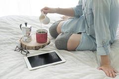 Кофе утра девушки выпивая на белой таблетке чтения кровати в высоких чулках Стоковые Фотографии RF