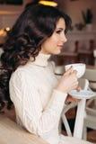 Кофе Чай или кофе красивейшей девушки выпивая Чашка горячего напитка Брюнет в чае кафа выпивая, есть помадки Стоковые Фотографии RF
