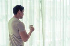 Кофе чая азиатского человека выпивая смотря вне к окнам утра Стоковое Фото