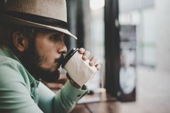 Кофе человека битника выпивая от устранимого бумажного стаканчика сидя на Стоковые Изображения RF