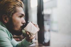 Кофе человека битника выпивая от устранимого бумажного стаканчика сидя на Стоковые Фотографии RF