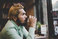 Кофе человека битника выпивая от устранимого бумажного стаканчика сидя на Стоковое фото RF