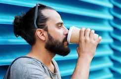 Кофе человека выпивая от бумажного стаканчика над стеной Стоковое фото RF