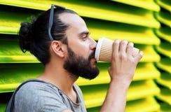 Кофе человека выпивая от бумажного стаканчика над стеной Стоковые Изображения RF