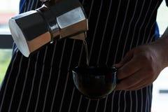 Кофе человека лить от бака Стоковая Фотография RF